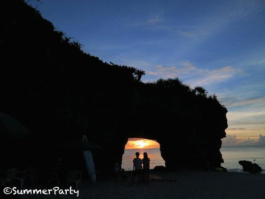 砂山ビーチ アーチの真ん中に落ちる夕陽とカップル